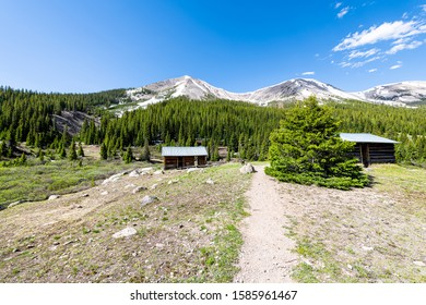 Independence Pass mining townsite buildings cabins in White River National Forest in Colorado with green pine trees and snow mountain peaks wide angle