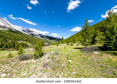 Independence Pass mining townsite wide angle view of cabins in White River National Forest in Colorado with green pine trees and snow mountain peaks