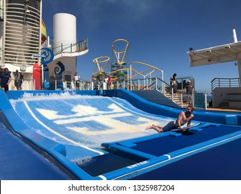 INDEPENDENCE OF THE SEAS - ROYAL CARIBBEAN - FEBRUARY 28, 2019: On Board cruise line guest takes boogie board ride on FLOWRIDER wave pool.