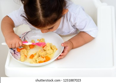 Independent adorable toddler girl eat soup with spoon. Child little toddler eats Delicious Matzoh ball soup Jewish traditional cuisine, homemade Matzo Ball soup with vegetables. Passover, shabbat food