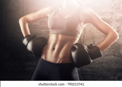 Independent fit woman with boxing gloves posing and showing strength.Victorious concept for equal rights without gender discrimination