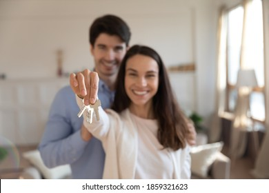 Independent life. Happy millennial family couple clients of bank broker realtor buyers renters tenants of new apartment house posing for portrait in living room looking at camera holding keys in hands