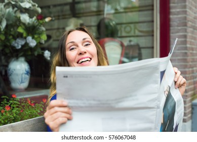 Independent middle aged woman reading a newspaper outside. A fake news concept.