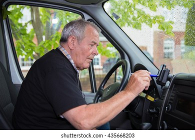 Independent retired senior working as courier setting satellite navigation in his transport van