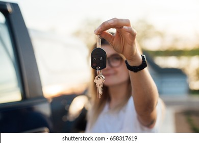 Independent young millennial hipster proudly shows keys from her car, huge american truck,as a symbol of american dream and success