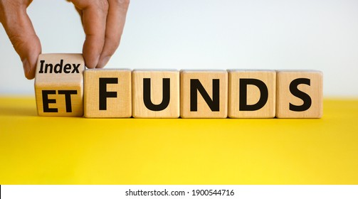 Index funds vs ETF symbol. Businessman turns a cube and changes words 'ETF' to 'Index funds. Beautiful yellow table, white background, copy space. Business and ETF and index funds concept.