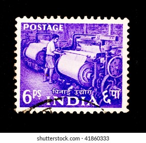 INDIA - CIRCA 1923: A stamp printed in India shows image of an Indian man working a weaving loom, series, circa 1923
