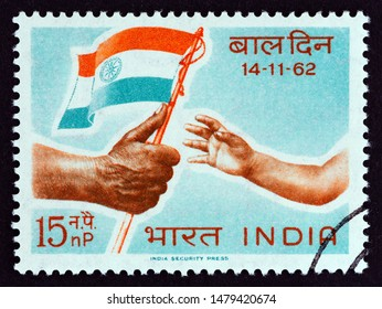 """INDIA - CIRCA 1962: A stamp printed in India from the """"Children's Day"""" issue shows child reaching for flag, circa 1962."""