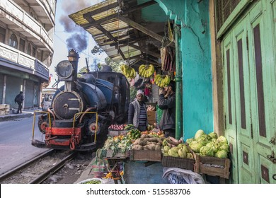 INDIA, DARJEELING, 31-10-2016: Toy train passing a market stand near Ghoom with only a few inches clearance,