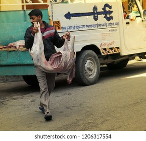 India, Dharamsala - March 10, 2018: delivery of meat in a butcher's shop in Asia, man carries a sheep carcass without skin and entrails