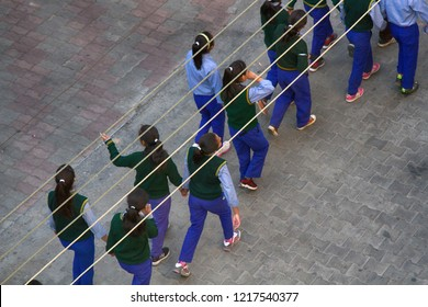 India, Dharamsala - March 10, 2018: A group of Schoolgirls uniform lined up in pairs. The view from the top. With wires girls resemble musical notation, figuratively score parthenia (sheet music)