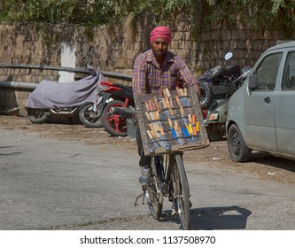 India, Dharamsala - March 11, 2018: Knife salesman. Trade on the go with a bike where a stand with knives is fixed