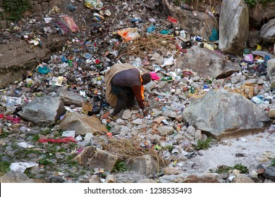 India, Dharamsala - March 12, 2018: Garbage collector (picker) at work. Selection of plastic and metalm unauthorized dump. Daily life of Indian villages