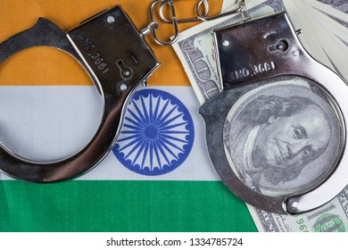 India flag with handcuffs and a bundle of dollars. Currency corruption in the country. Financial crimes