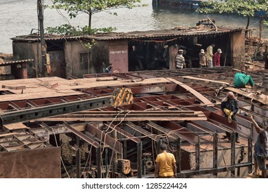 India, Goa - 31 March 2018: Berth construction at ship repair shop (dockyard), steel channel (channel iron; rocker bonding) construction. Workers, welders, fitters. Arabian sea