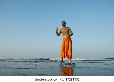 INDIA, GOA - AUGUST 17, 2009: Performance on the Arambol beach. Free lifestyle. Man juggling. A man in orange pants juggles with glass balls