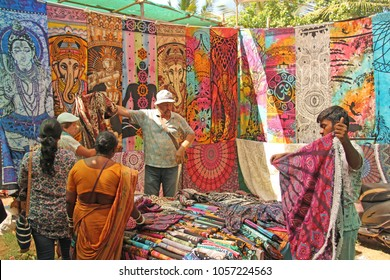 India, GOA, January 24, 2018. Indian man salesman in the Anjuna market, Goa, India. Indian markets, trade. A store of shawls and stoles.