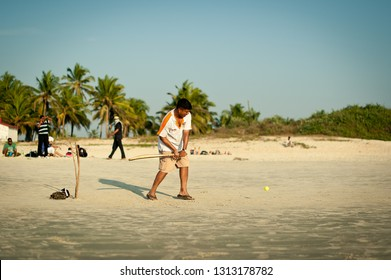 India, Goa - November 15, 2012: Friends play cricket on the beach of GOA in India. The guys play Indian baseball on the beach. Indian national sport. The game of cricket at sunset