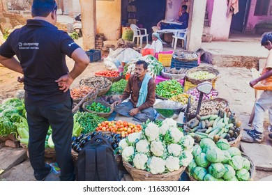 India, Govardhan, October 2016 :a man buys vegetables from a seller on the street market of India