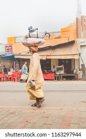 India, Govardhan, October 2016 :Indian Traveling monk carrying bags with things on his head along the street of the city