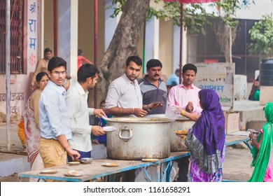 India, Govardhan, October 2016 :people in india on the street hand out free food from a large pot