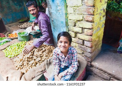 India, Govardhan, October 2016 : portrait boy along with his father sells vegetables on the street market in India.