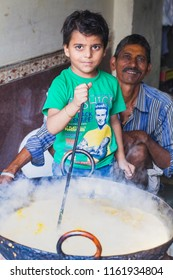 India, Govardhan, October 2016 : portrait boy and father prepare food in a large saucepan in a street cafe in India
