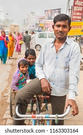 India, Govardhan, October 2016 :portrait of a man trishaw with his kid family sitting in bike