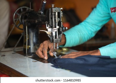 India, Govardhana, November 2016:Male tailor working on sewing machine atelier in india