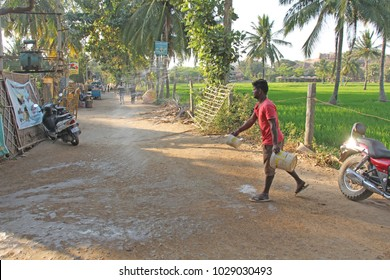 India, Hampi, 02 February 2018. The main street of the village of Virupapur Gaddi. Guesthouses overlooking the rice fields. An Indian man sprinkles water on the road. Drops of water in flight.