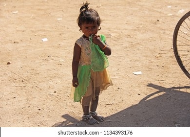 India, Hampi, 02 February 2018. A little poor girl in a dirty dress. Portrait of an indian girl. A girl from India in ornaments.