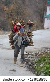 India, Himalayas - March 16, 2018: Undersized Sherpas carry large bundles of firewood on their backs along a mountain road. Daily life of Indians. Street photo sketches