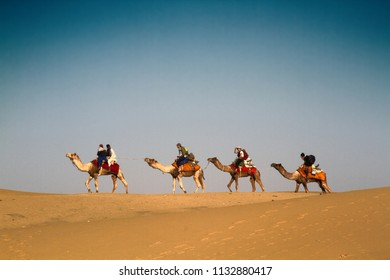 India, Jaisalmer - March 7, 2018: Caravan of single-humped camels dromedary with tourists. Exotic travel. The Great Indian desert (Thar)
