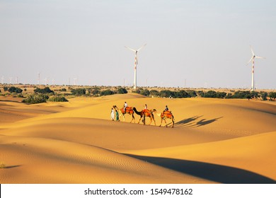 India, Jaisalmer - March 7, 2018: cameleers camels for tourists. The Great Indian desert (Thar). Now even in the desert came technological progress (wind turbines) and radically changed its appearance