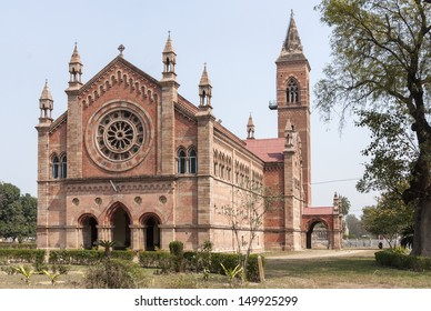 India Kanpur: All Souls Church in its park with tower and rose-window. Classic dominant red brick cathedral building set in green environment and under blue skies.