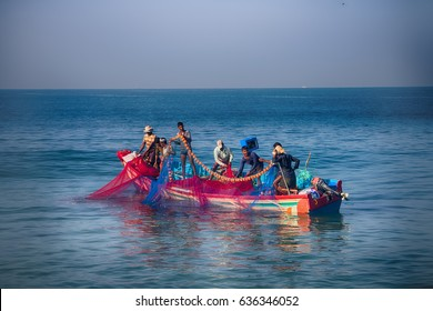 India, Kerala - December 27, 2015: Indian fishermen graphically pull painted Seine right in boat. Net painted in bright colors and seined fish. Collective fishery