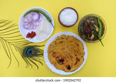 India Makki roti and sarson saag with onion chilly salad and earthened glass of sweet lassi in an authentic way with white butter and green chilly. Punjabi traditional style food