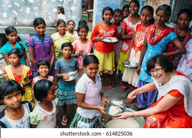 India - March 11, 2015: Missionary woman serve rice to indian girls in a school