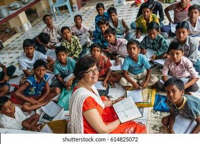 India - March 11, 2015: Missionary woman teach poor rural indian children in the school