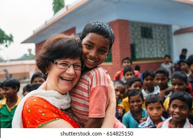 India - March 11, 2015: Missionary woman hugging poor rural indian child in the school