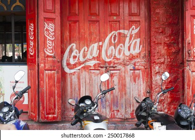 INDIA, PUNE, 25 November 2014: Red door with logo Coca-Cola and motorcycles.