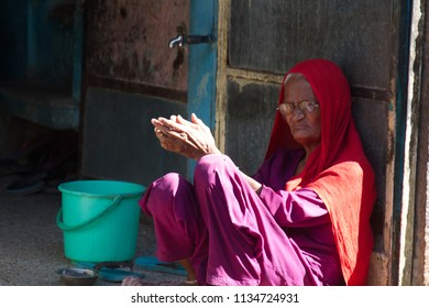 India, Pushkar-March 4, 2018: Poor old woman with a decent expression in red head wrap, piercing the nostrils, worthy old age