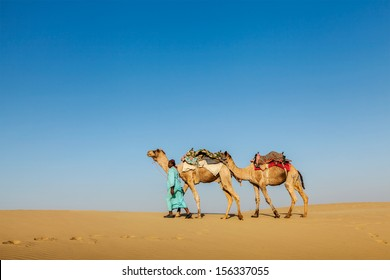 India Rajasthan travel background - Indian cameleer (camel driver) with camels in dunes of Thar desert. Jaisalmer, Rajasthan, India