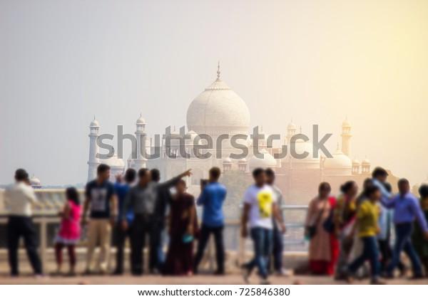 India Taj Mahal and sun light with blur of crowd of tourists enjoying walking around for take a photo.