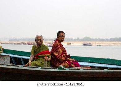 India, Varanasi - March 20, 2018: Portraits of two Indian women during pilgrimage to holy city on Ganges river in boat, special not everyday clothes of pilgrims. Sacred water of river Ganges.