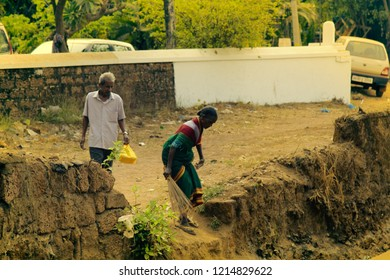 India, Vasco da Gama - 5 April 2018: not equipped ditch crossing to railroad. Mature Indian couple moves through ditch on village street. Daily life Indian cities and villages, street photo sketches