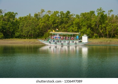 INDIA, WEST BENGAL, SUNDARBANS, 12-08-2015. tourists enjoying a ride with an excursion boat through the extended delta of river Ganges which in parts is a UNESCO world heritage site.