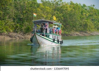 INDIA, WEST BENGAL, SUNDARBANS, 12-08-2015. tourists enjoying a ride with an excursion boat and a guide through the extended delta of river Ganges which in parts is a UNESCO world heritage site.