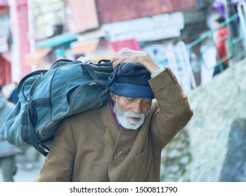 India, Western Himalayas - March 18, 2018: an elderly man carries a bag on his shoulder, purchasing. Daily life of Indian people