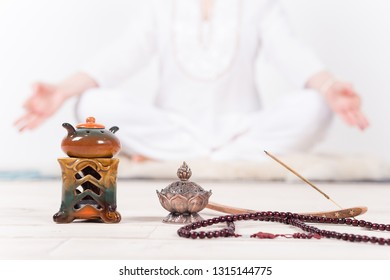 Indian accessories for meditation and yoga, prayer beads, oil burner, incense in the background of the meditator girls